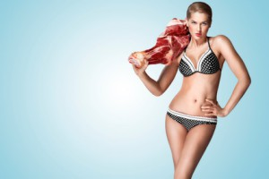 A conceptual photo of self-confident pin-up girl in bikini holding big piece of meat.